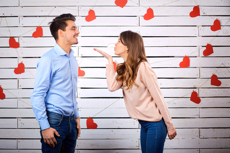 Young couple on Valentines Day. The girl makes an air kiss to her boyfriend.