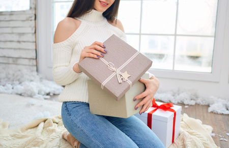 The girl at the window with gifts in the winter. A young woman looks at the box on Christmas day. Stock Photo