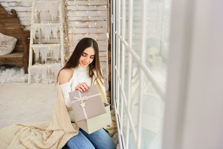 The girl at the window with gifts in the winter. A young woman looks in a Christmas box. Stock Photo
