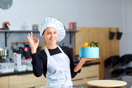 A confectioner woman with a cake in her hands in the kitchen in a pastry shop.