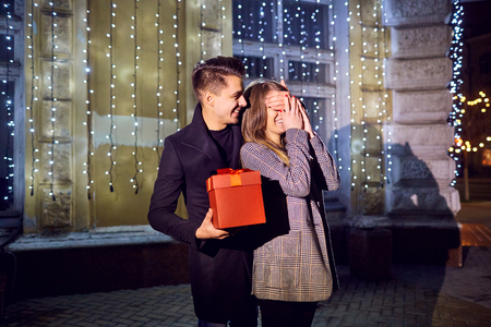 A guy gives a gift to a girl at night on a city street outdoors. Couple in love. Valentines Day.