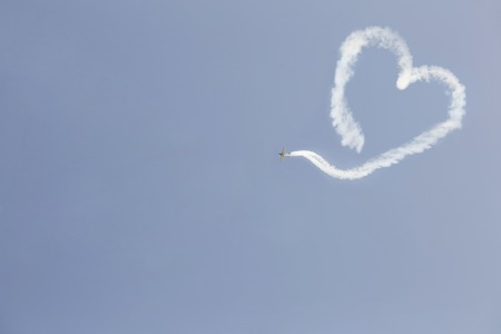 A flying airplane with smoke in the form of a heart. Valentines Day.