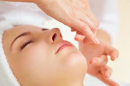 Piękna kobieta na masaż twarzy w salonie spa.