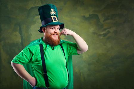 Een dikke man met een baard in St. Patricks pak lacht op een groene achtergrond.