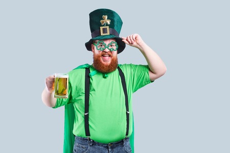A fat man with a beard in St. Patricks suit is smiling with a mug of beer on a gray background. Stock Photo