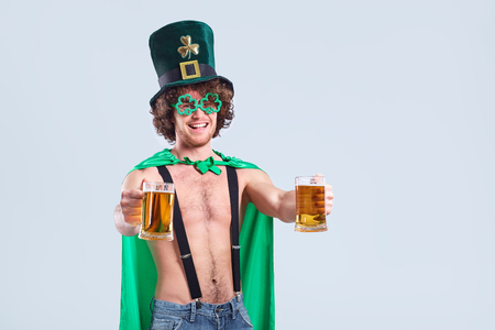 A young curly-haired man in the suit of St. Patrick with a mug of beer in his hand on a gray background.