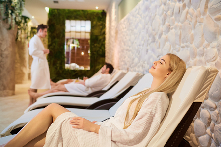 People in bathrobes are resting in the spa salon. Friends relax on weekends. Stock Photo