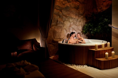 A loving couple with a glass of champagne in a jacuzzi with candles relax.