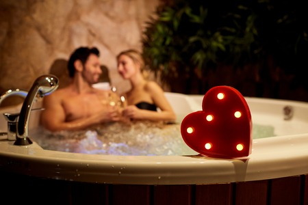 Heart on a background of a romantic couple with champagne in the hot tub. Valentines day.