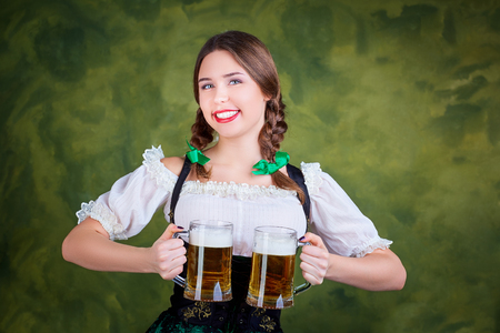 Young girl waitress oktoberfest in national costume with a mug of beer in her hand. St. Patricks Day.