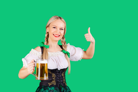 Girl waitress oktoberfest in national costume with a mug of beer in her hand. St. Patricks Day. Stock Photo