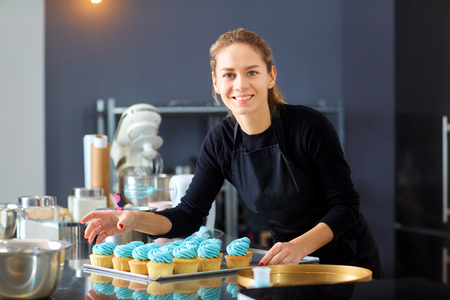 Confectioner pastry woman holding a tray of cakes in the kitchen. Standard-Bild