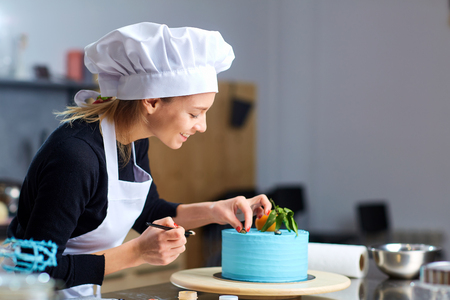 A confectioner woman decoration a cake  in kitchen a pastry shop.