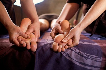 Massage in four hands on feet in the spa salon. Two massage therapist make massage for a woman.