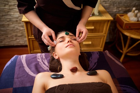 Stone massage is a facial massage for a woman in the beauty center. Stock Photo