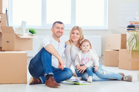 A happy family moves to a new apartment. Mother, father and child with boxes in the room of the new house. Stock Photo