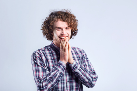 Curly-haired guy surprised rejoices with a positive emotion on a gray background.