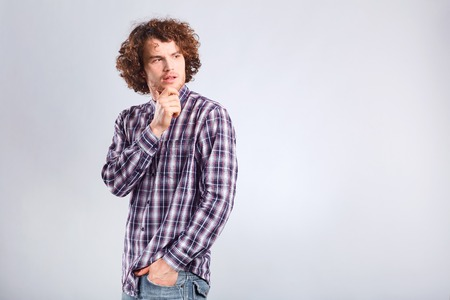 A curly-haired guy thinks with a serious emotion on a gray background.