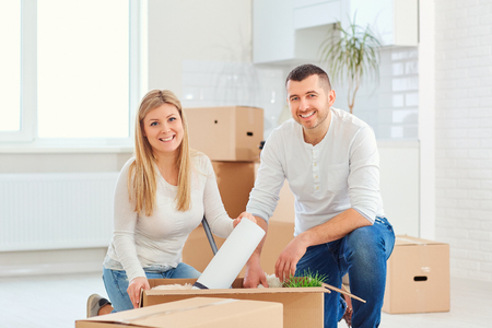A couple with boxes moves to a new house. Property For Sale. Stock Photo