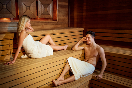 Pareja en toallas descansando en la sauna. Hombre y mujer en un salón de spa.