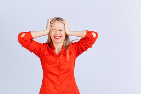 Young blond woman in an everyday with headache problems on a gray background. Stok Fotoğraf