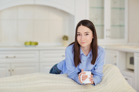 Young serious girl with a cup of hot drink in the kitchen. Stock Photo