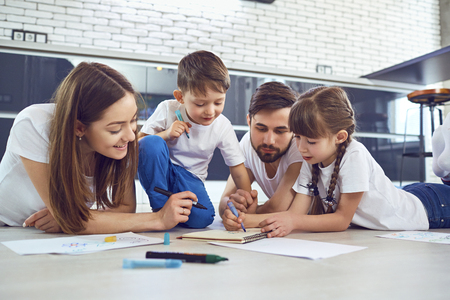A family draws on paper lying on their free time on the floor in the room. Stock Photo