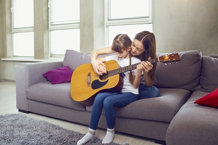 Mom teaches a kid girl to play an acoustic guitar while sitting on the sofa in the room.