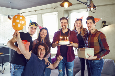 A group of friends with a torus with candles at a birthday party in a room.