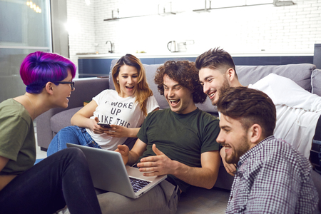 A group of friends of students in leisure with a laptop together in a room.