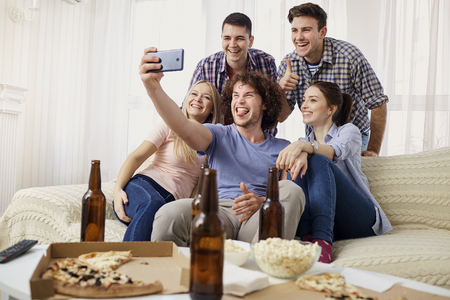 A group of friends are photographed on a camera indoors. Stock Photo
