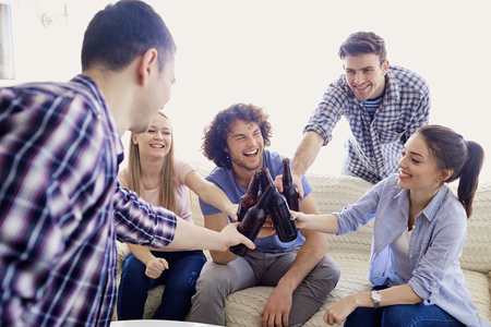 A group of friends are clinking bottles at a meeting in the room. Stock Photo