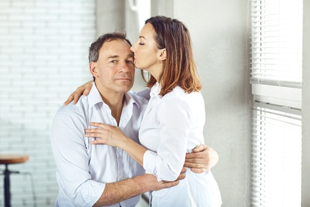 Mature couple happy hugging indoors. Happy family.