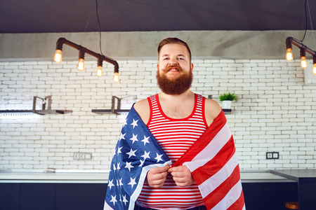 A fat man with a beard with an American flag. Day of independence of America. Stock Photo