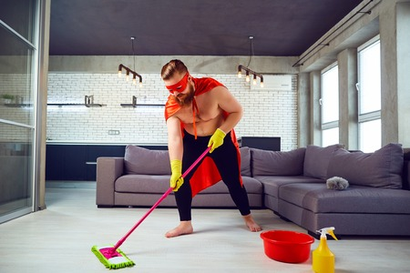 A fat, funny man in a superhero costume is cleaning the house. Cleaner is a super hero in the apartment.