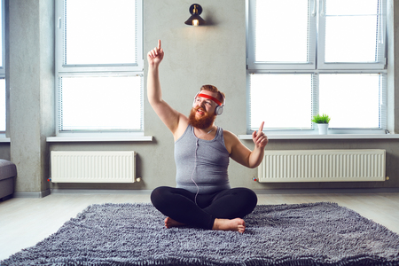 A funny posirive fat bearded man in the headphones does yoga in the room. Stock Photo