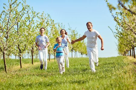 Happy family having fun walking in the garden in spring, summer. Mother, father and sons in nature.