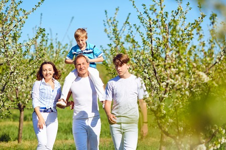 A happy family walks in the garden in spring, in the summer. Mother, father and sons in nature.
