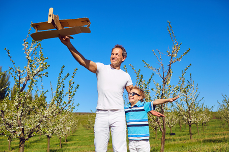 Father and son with a plane stand in a flowering garden in spring, summer in nature. Stock Photo