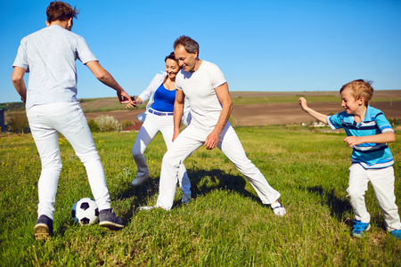 Happy family playing with a ball on nature in spring, summer.Mother, father and sons in the field.