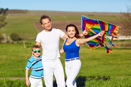Happy family with a kite on nature in spring, summer.Mother, father and sons in the field.
