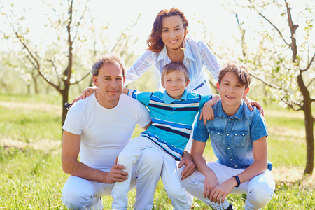 Happy family sitting on nature in spring, summer.Mother, father and sons in the field. Stock Photo