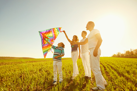 Happy family playing with a kite on nature in spring, summer.Mother, father and sons in the field.