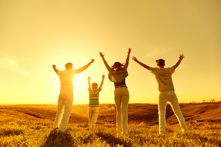 Happy family with raised hands on nature at sunset in the evening.