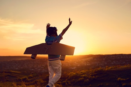 A happy boy in a superhero costume is playing with an airplane on the nature at sunset. Stock Photo