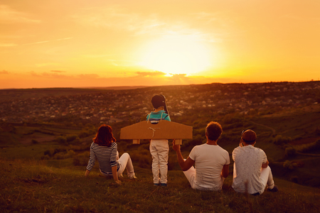 Happy family with nature in the evening at sunset.