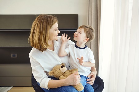 A beautiful grandmother with a grandson child in the room. Stock Photo