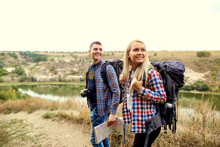 A young couple of tourists  with a map in a hike in nature.