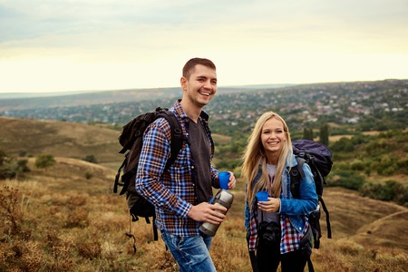 A happy couple of travelers are drinking tea from a bottle in nature. Stock Photo
