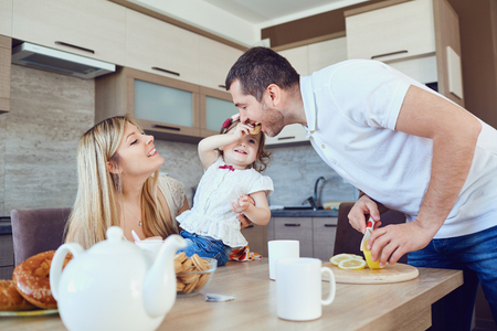 A happy family is eating in the kitchen while sitting at a table. Stock Photo